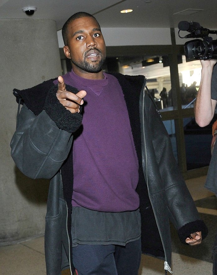 Kanye West smiles and chats with photographers as he departs LAX