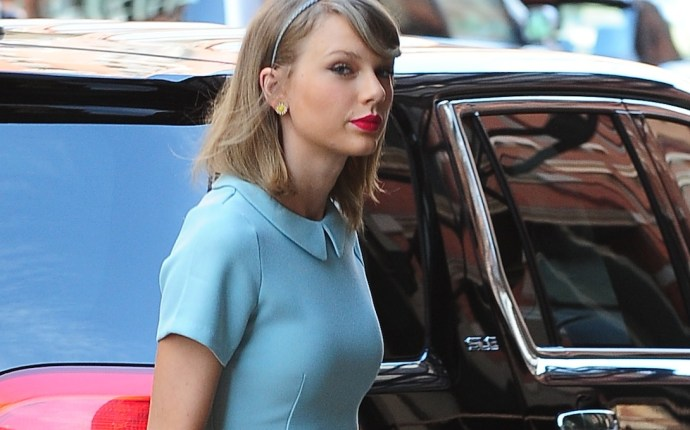 Taylor Swift arrives home wearing a green dress, peach shoes and carrying a yellow tote bag in NYC