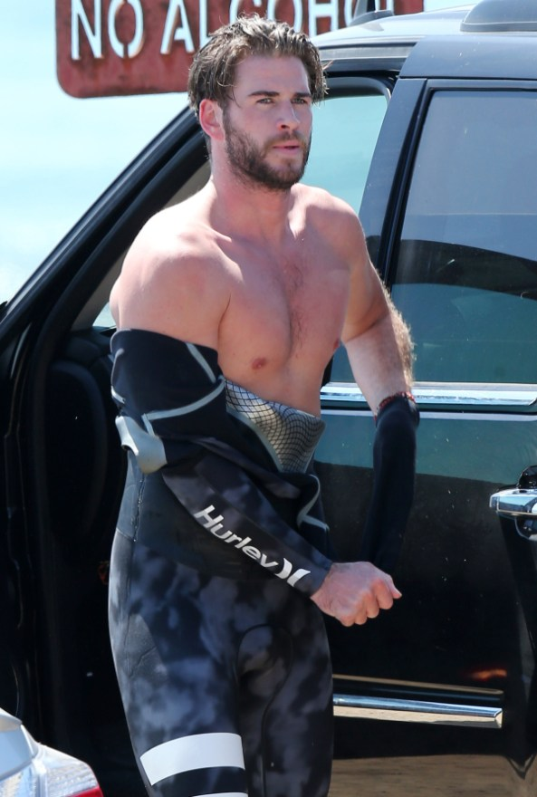 EXCLUSIVE: Liam Hemsworth showing off his muscles as he surfs with a friend in Malibu