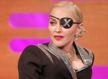 Madonna wearing a bejeweled X eye patch and a bedazzled jacket