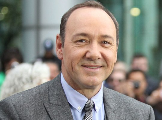 Kevin Spacey Smiling at Camera Wearing Lavendar Shirt, Black And White Tie, Gray Suit