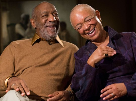 Smiling Bill Cosby Wearing Brown Shirt and Sweater Sitting With His Laughing Wife Camille Cosby Wearing Purple Blouse