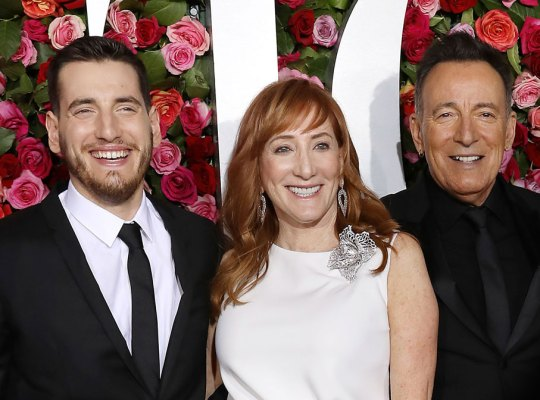 Sam Springsteen Wearing Black Suit and Tie, White Shirt Standing With Parents Patti Springsteen Wearing White Gown With Diamond Drop Earrings, and Bruce Springsteen Wearing Black Suit, Tie and Shirt
