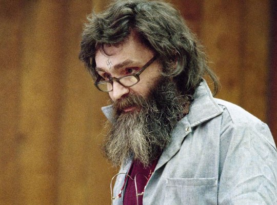 Charles Manson in Courtroom Wearing Reading Glasses, Maroon T-Shirt And Denim Shirt, Arunf his neck are Additional Pair of Glasses