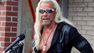Duane Dog Chapman Speaking To Press Wearing Sunglasses and Leather Trim Track Jacket