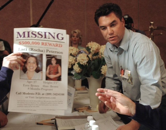 Scott Peterson At Table With Wearing Plaid Shirt Leaning Over Table With Posters Of Missing Pregnant Wife Lace (and Connor)